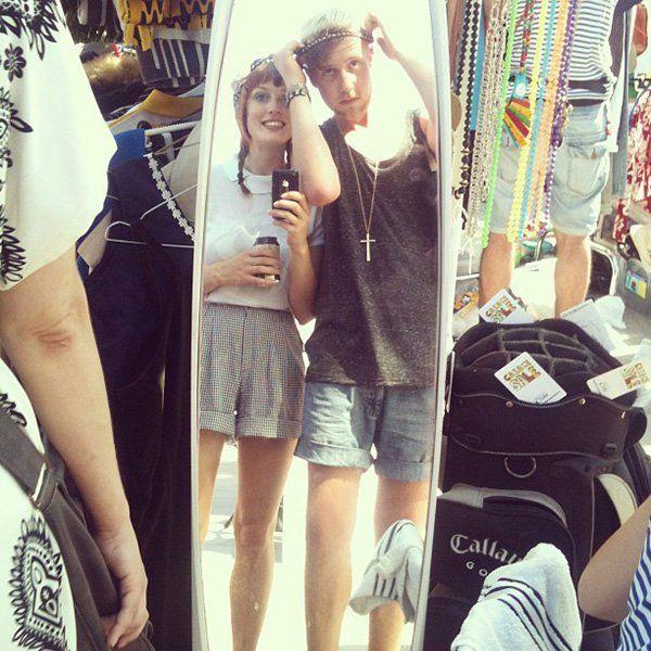 hipsters gafapastas mirándose en el espejo de un mercadillo de ropa usada