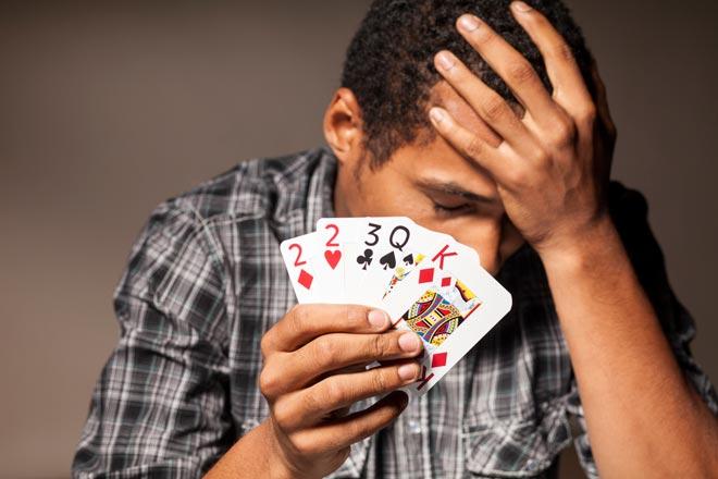 chico con unas cartas de poker malas