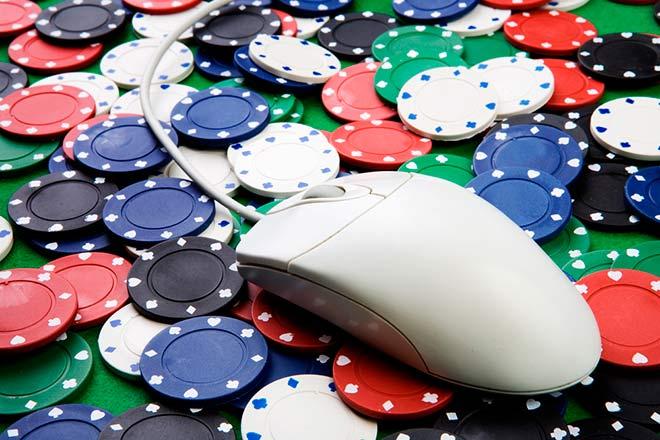 ratón de ordenador encima de un tablero de poker con fichas