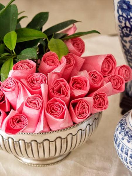 idea de centro de mesa hecho con servilletas enrolladas con forma de rosas