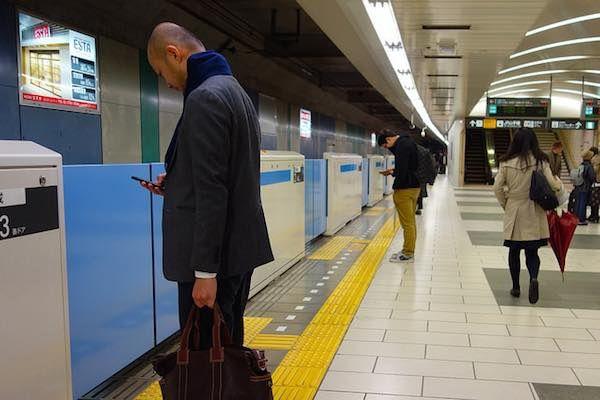 jugando con el móvil en el metro