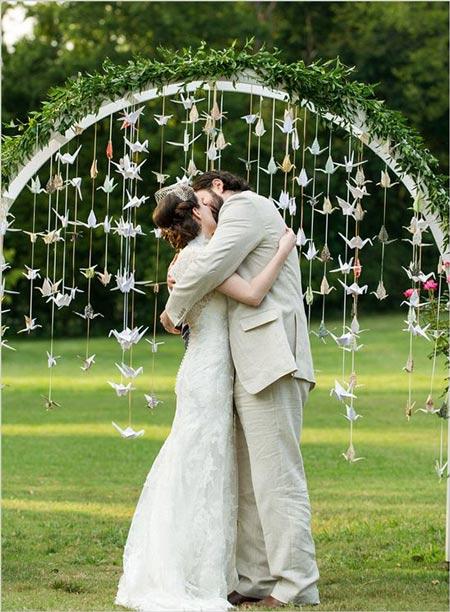 cortina con grullas de origami para decorar altar en una boda