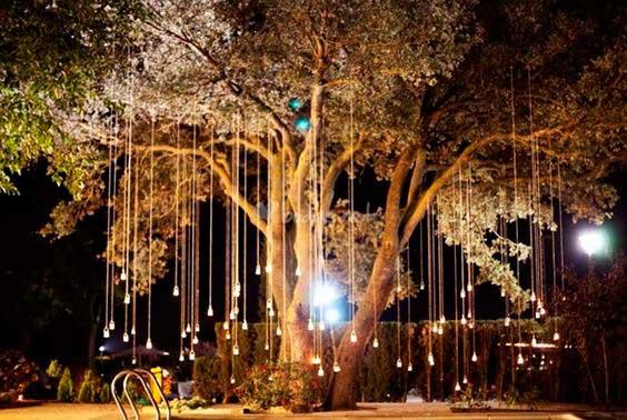 forma original de iluminar una boda de exterior colgando luces de los árboles