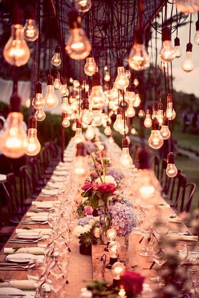 decoración original con bombillas colgando sobre la mesa del banquete de boda