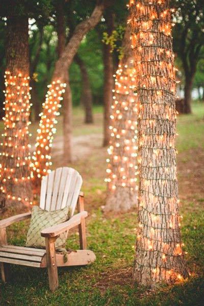 patio de una boda decorado con árboles con guirnaldas en el tronco