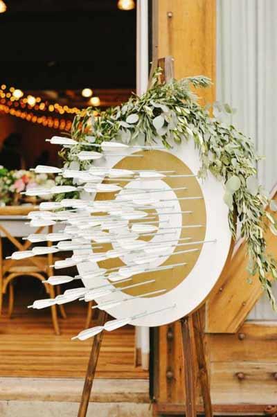 """decoración para boda con """"Encuentra tu mesa"""" de una diana y flechas"""