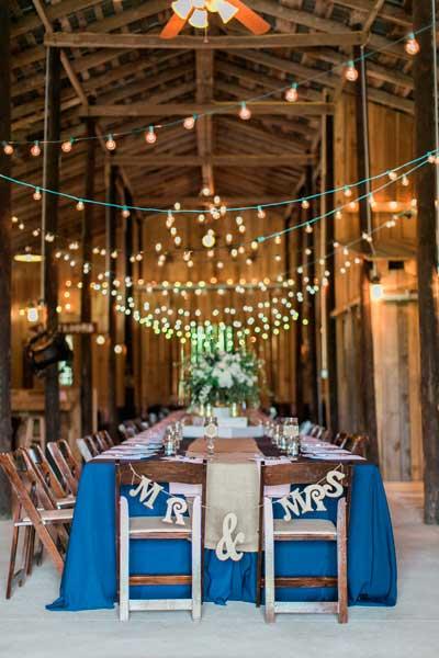 guirnalda de luces en zig zag para decorar el techo de una boda de interior rústica