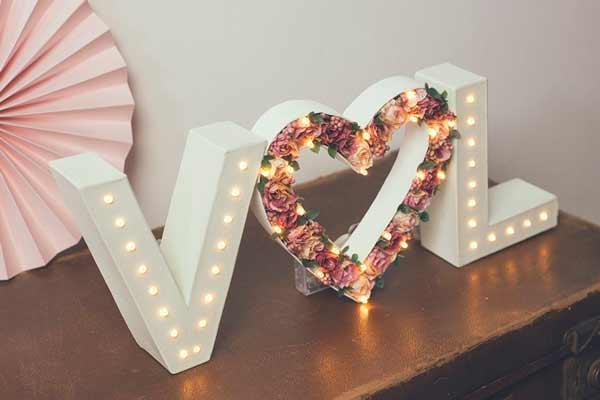 iniciales de los novios hechas de cartón pluma con flores y luces