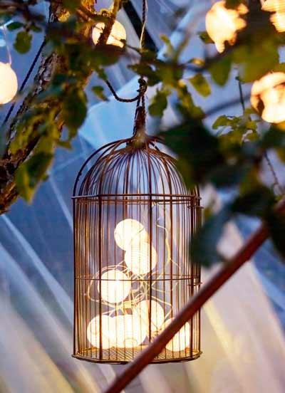 idea para decorar en una boda exterior con una jaula y una guirnalda de luces de bolas