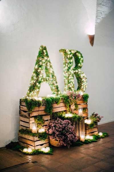 iniciales forradas con plantas y tiras de luces para decorar la entrada de una boda o photocall