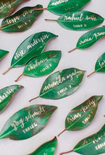 hojas de árbol decoradas y barnizadas para utilizar como tarjetas marcasitios para el banquete de una boda