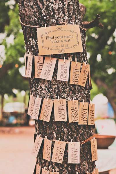 distribución del seating plan con etiquetas en el tronco de un arbol, para boda