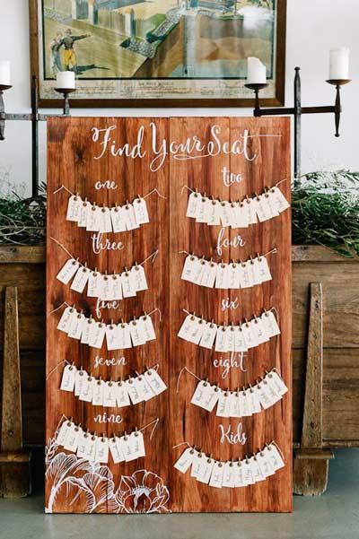 idea de decoración para boda rústica con el mural de invitados de madera con etiquetas