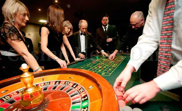 jugadores apostando en una ruleta americana de doble cero