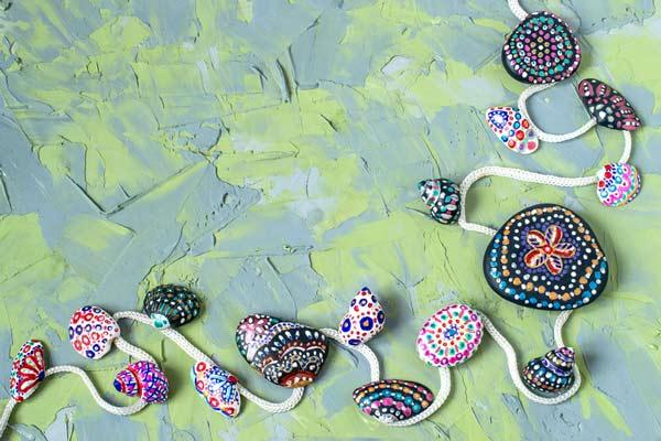 guirnalda con piedras, conchas y caracoles pintados