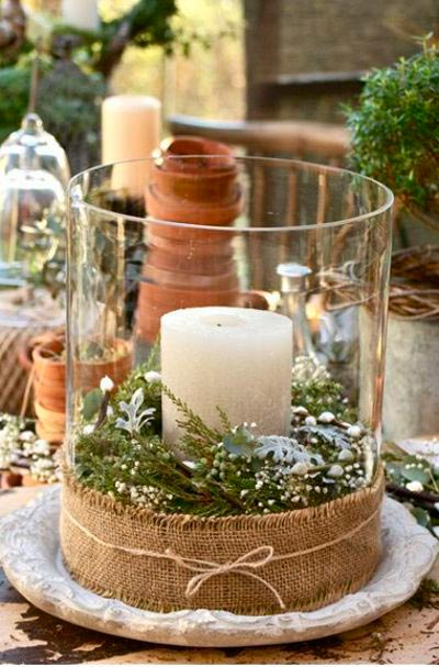 Jarrón de cristal sencillo para decorar la mesa con un cirio y plantas de navidad