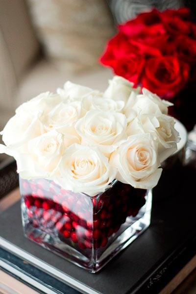 Centro floral con rosas blancas y rojas y arándanos en la base.
