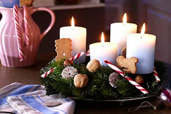 Centro de mesa con dulces de Navidad y cirios blancos