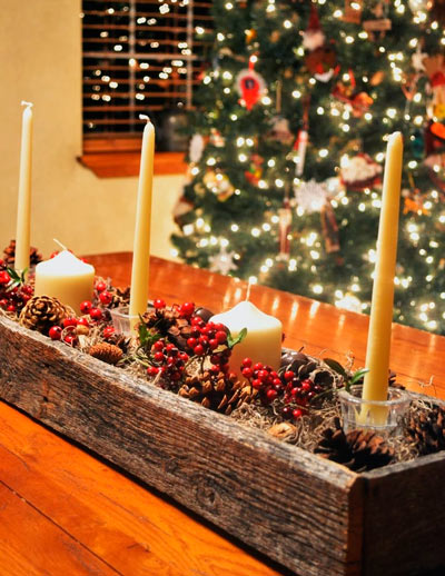 centro de mesa de madera con plantas de navidad y velas