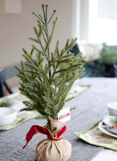 Mini árbol de navidad para la mesa con hojas de pino atadas