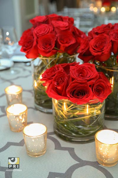 Centros con rosas rojas y los tallos en un jarrón de cristal