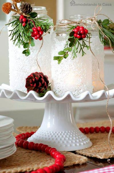 Manualidad de portavelas a partir de tarros de conservas con falsa nieve y muérdago