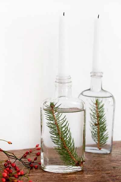 centro de navidad con Botellas grandes de cristal con una hoja de pino y una vela