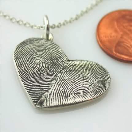 colgante con forma de corazón y las huellas dactilares de dos personas