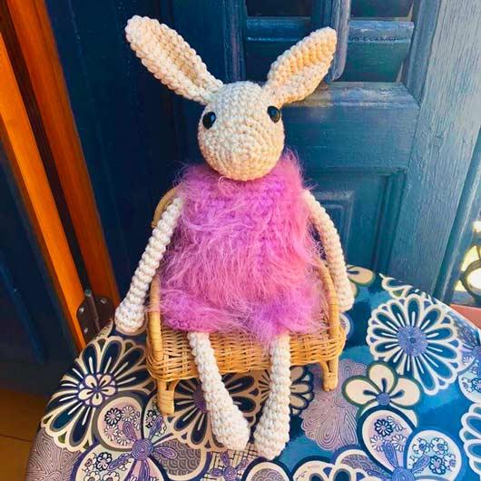 muñeco personalizado de una oveja sentada en una silla con un vestido de pelos