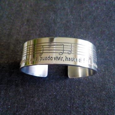pulsera personalizada grabada con la partitura de una canción y la letra