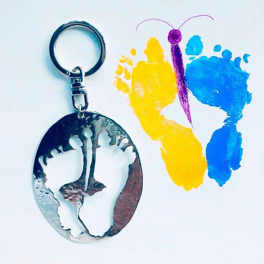 llavero personalizado con la forma de las huellas de unos pies hechas previamente en pintura