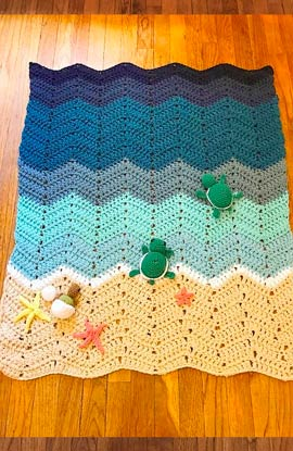 manta crochet para bebés con forma de playa, y tortugas y estrellas de mar de ganchillo